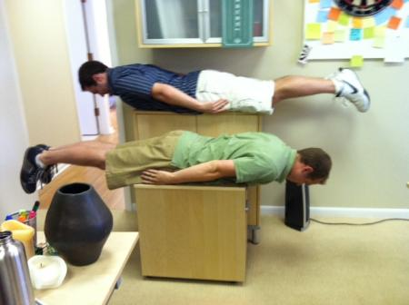 Jack and coworker plank in snazzy biz shorts